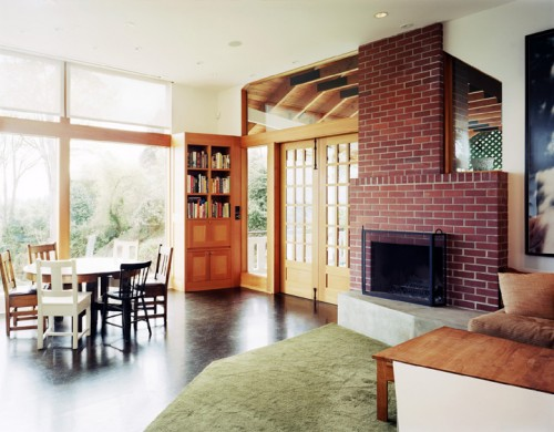 French doors and floor-to-ceiling windows overlook a hill heading down toward Lake Washington. Courtesy Tom Fowlks