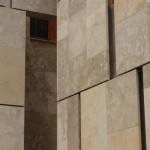 Galllery windows peak out from under limestone facade panels.