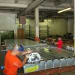 Craftsmen add the cold-formed steel decking layer to the panels (Radius Track)