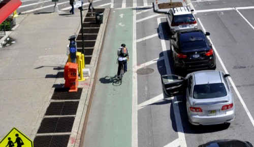 The 8th Avenue Complete Streets program keeps cyclists safe from cars and car doors. (Courtesy NYCDOT)
