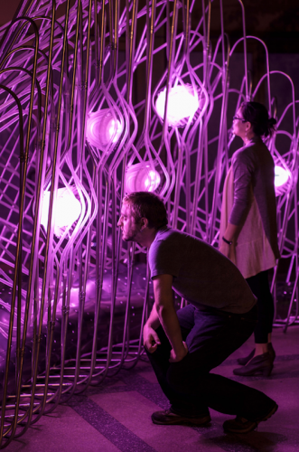 Visitors read the brightly lit data pods; The brighter the pod, the stronger the data trend. (Future Cities Lab)