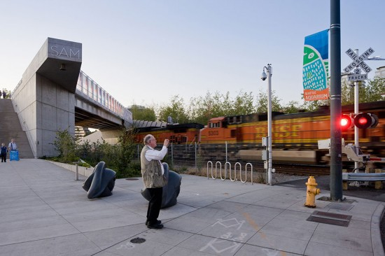 View of the Olympic Sculpture Park from Broad Street showing freight train, bridge, and Louise Bourgeois's Eye Benches. (Iwan Baan)