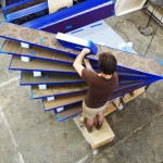 A team member from The Guild sequentially fastens labeled, fabric-covered slats to the rib. (courtesy The Guild)