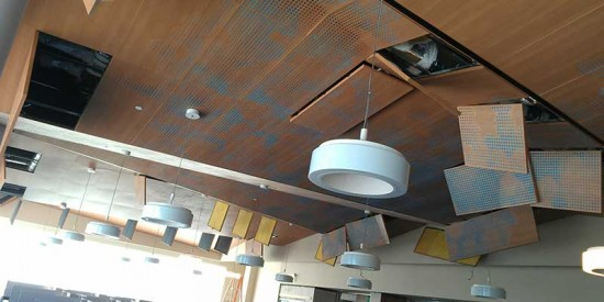Affixing the panels with torsion springs maintains access to the ceiling cavity to maintain the HVAC system, ductwork, and other mechanicals. (courtesy Ceilings Plus)