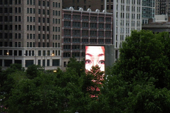 The dynamic Crown Fountain peeks over the treetops of Millennium Park. (John W. Iwanski / Flickr)