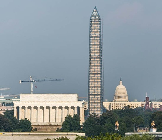The Washington Monument stands covered in scaffolding between the Lincoln Memorial and the U.S. Capitol. (ehpien / Flickr)