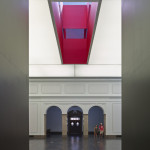A red skylight cutting through the top floor adds a pop of color to the otherwise restrained space. (Timothy Hursley)