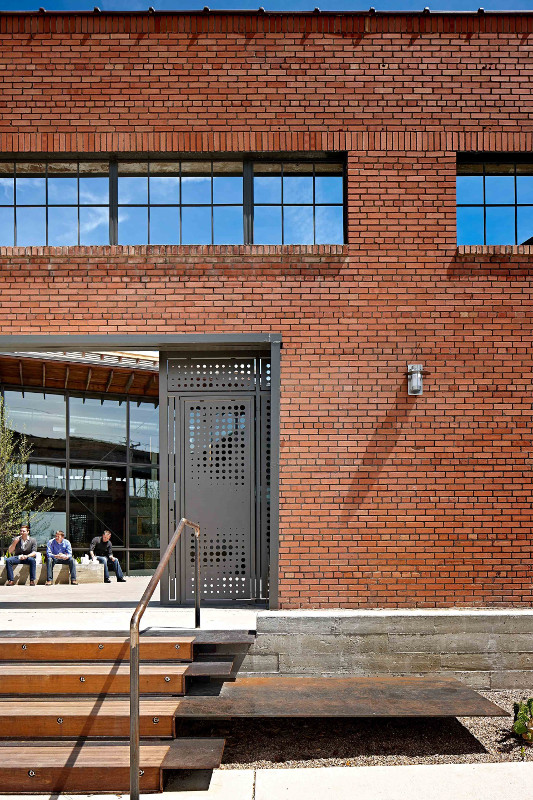 A new courtyard, framed by custom steel gates, floods the building with light and acts as a community gathering space. (Courtesy Overland)