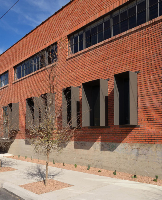 The architects punched new windows, extruded to reduce solar game, into the existing brick facade. (Courtesy Overland)