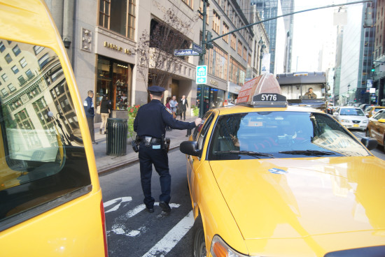 An NYPD officer telling a cab driver about New York City's new speed limit. (Courtesy NYC DOT)
