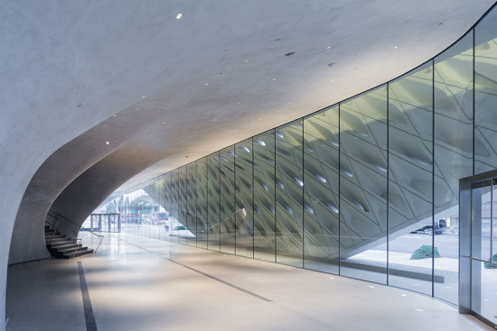 The ground-level lobby is a cave-like space with curving walls of hand-troweled plaster over steel framing. (Iwan Baan)