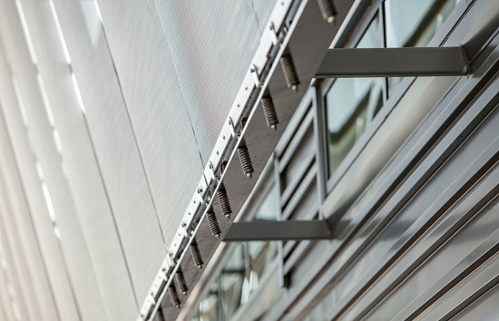 High precision assembly of rigid metal mesh panels suspended in tension off a steel frame structure (courtesy Cambridge Architectural)