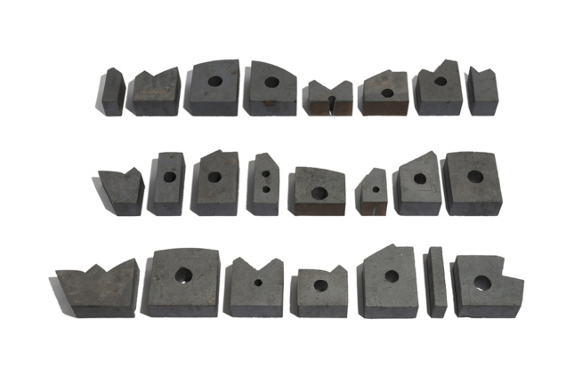 Photo of a layout of differently shaped bricks with holes in the center used in Bureau de Change's interlock project.