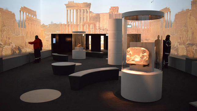 Installation view of some archeological fragments and large projections on gallery walls