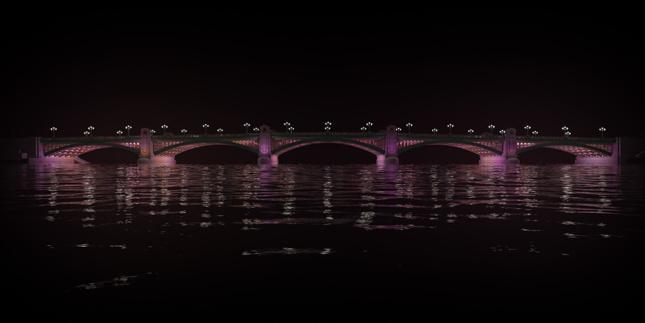 Side view of a lit-up bridge.