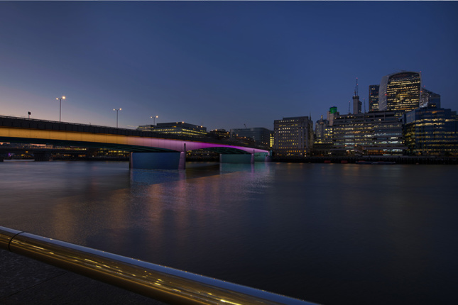Oblique view of London Bridge with colorful lighting.