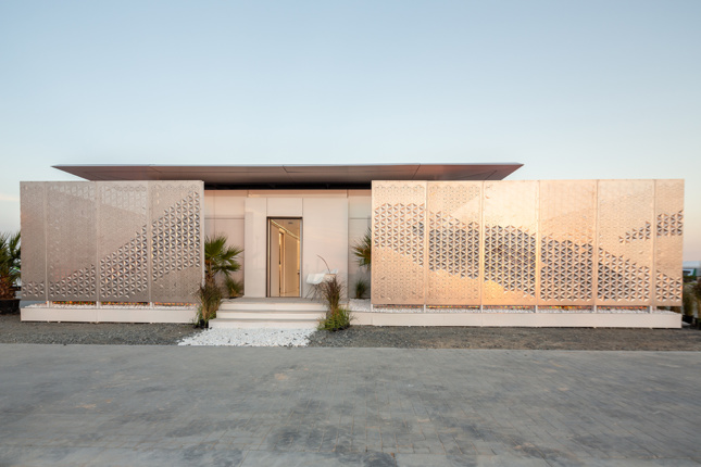 A view of a single level home in the Desert with a screened courtyard