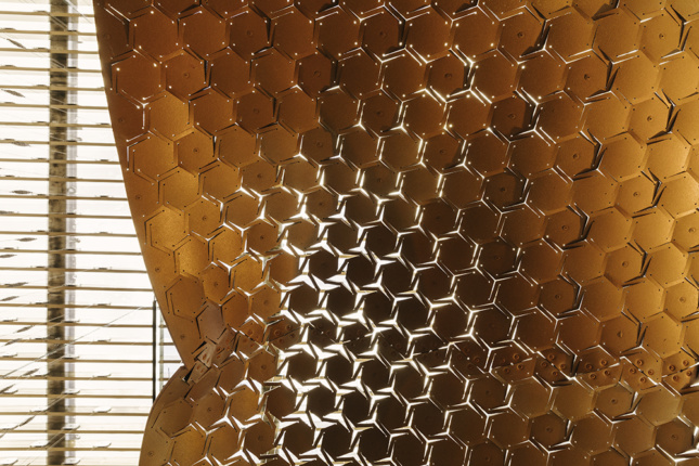 Photo of light shining through a mesh of ochre rubber-concrete that is deformed unevenly