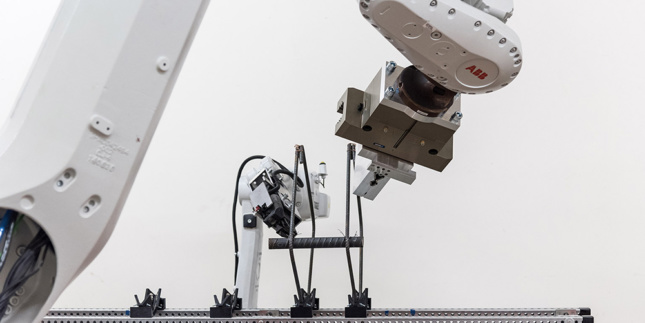 Photo of two robot arms bending pieces of steel