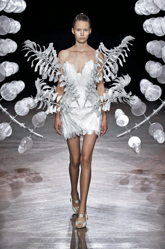 A model walks through the Omniverse sculpture by Anthony Howe wearing a white dress with symmetrical metal bands of rotating silk leaves