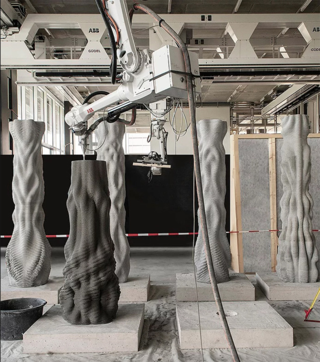 A robotic arm deposits concrete on a half-complete columns. Four completed columns stand behind it inside the fabrication space.