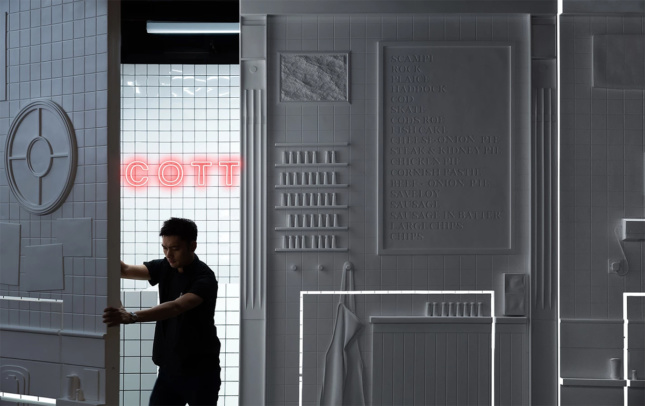 A person swings open a large white door panel, the wall adjacent to them is all white but appears as a wall in the kitchen with various fixtures. Behind them is a white tile wall with a red neon sign.