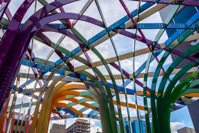 A view through different colored pieces of aluminum interwoven into a canopy.