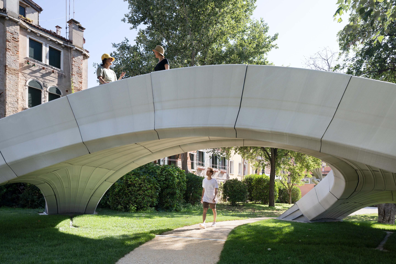 people explore a 3d-printed concrete arch footbridge located in a park