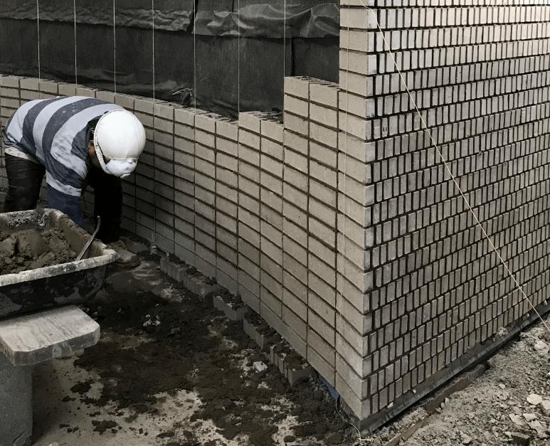 masonry worker installing the brick facade at 932 grand street