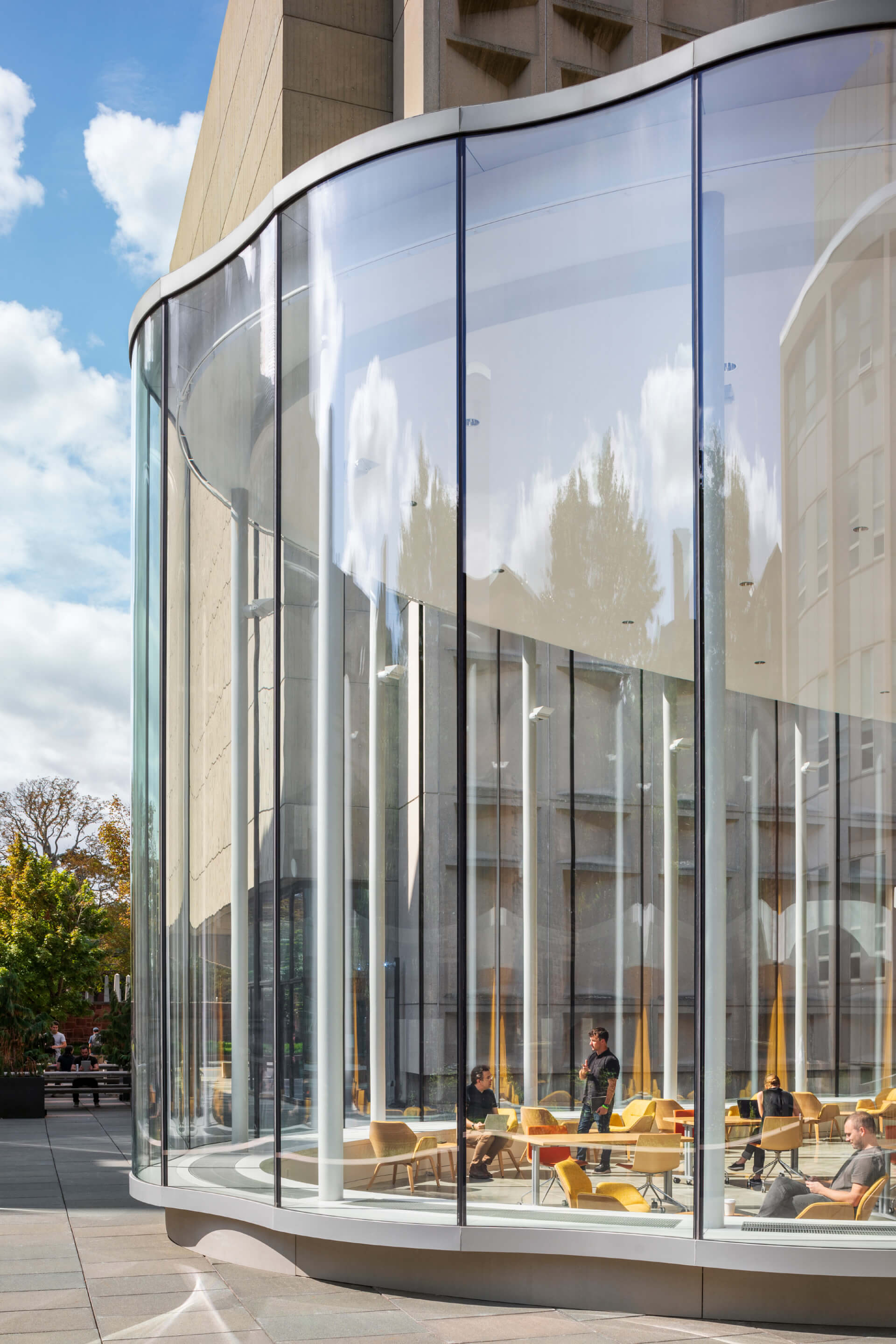 A double-height glazed entrance lobby with curved and scalloped glass panels made from float glass