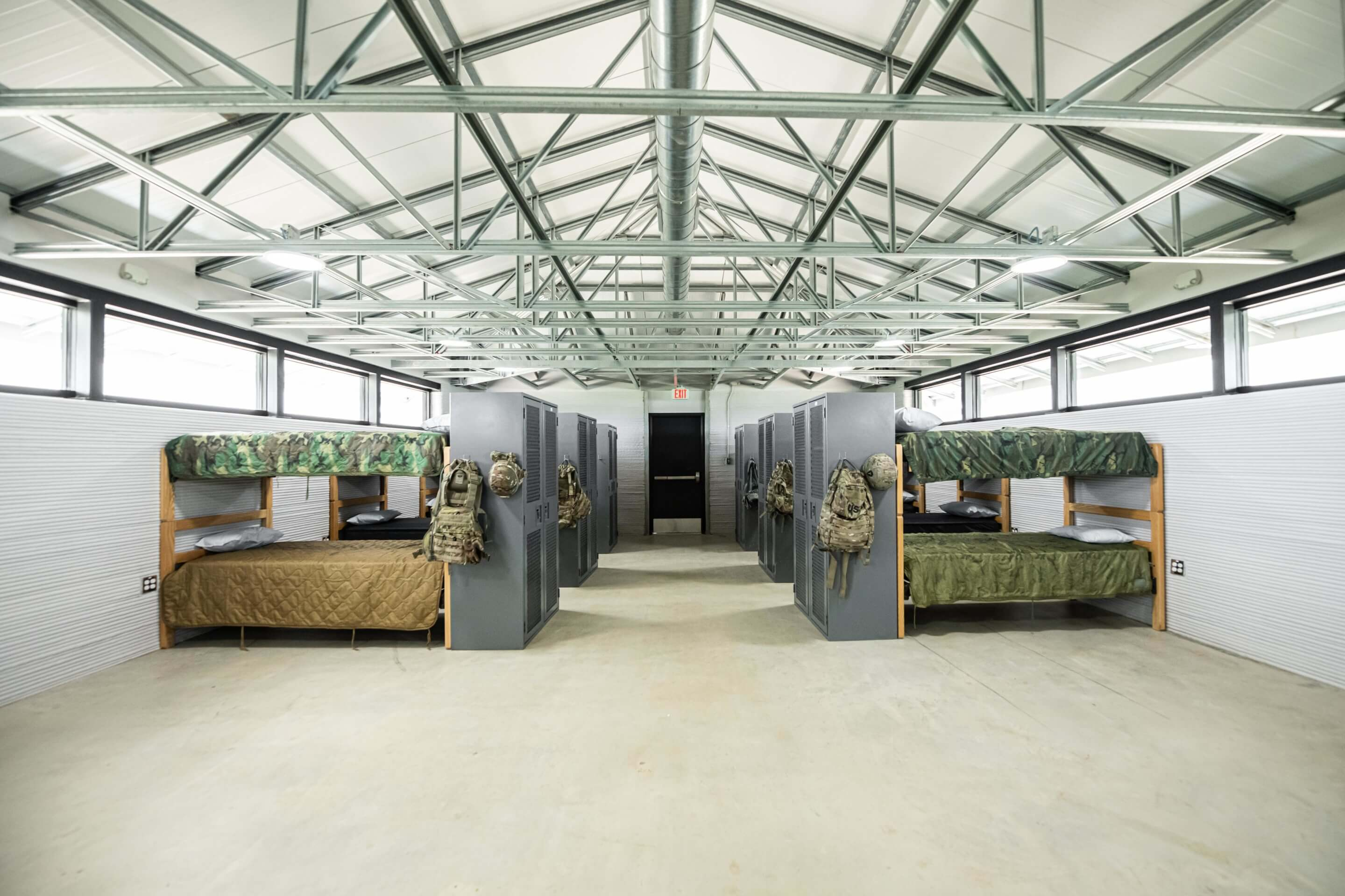 large room with bunk beds and army fatigues