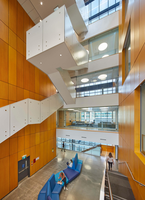 A tall vertical atrium with orange walls